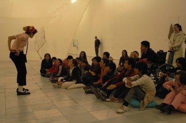 La contadora de cuentos y un grupo de asistentes en una de las salas de la exposición Adolfo Schlosser. 1939-2004