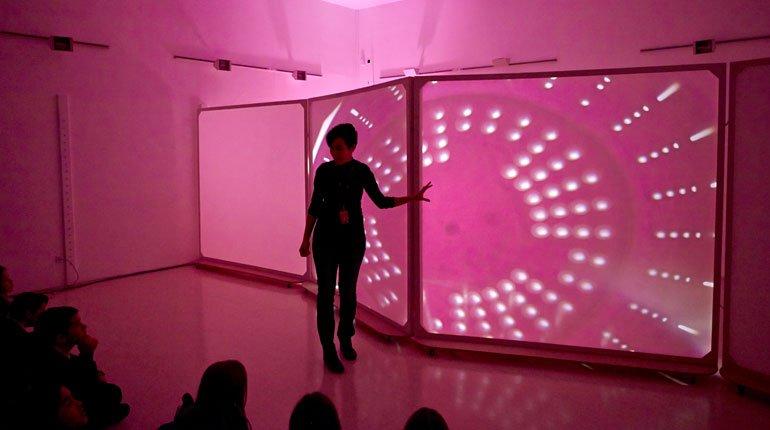 La educadora introduce en el taller de sombras a los alumnos