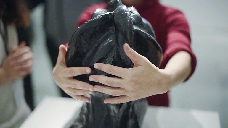 Persona ciega explorando una escultura durante la actividad