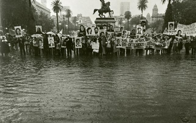 Daniel García. En una Plaza de Mayo inundada, frente a la Casa de Gobierno, los familiares portan las fotos con los rostros de los desaparecidos, 1983